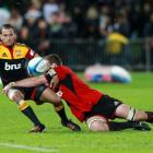 Aaron Cruden of the Chiefs gets a kick away while being tackled during the round three Super...