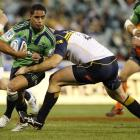 Aaron Smith of the Highlanders is tackled by Stephen Moore of the Brumbies.  (Photo by Stefan...