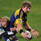 Highlanders blindside flanker Adam Thomson is tackled by Cheetahs hooker Adriaan Strauss during...