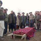 Afghan men stand around the body of a victim who was killed in a suicide attack in Takhar...