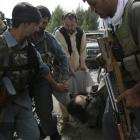 Afghan police men carry the body of suicide bomber wrapped in a carpet inside governor's compound...