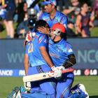 Afghanistan's Shapoor Zadran is congratulated by team-mates Hamid Hassan (right) and Usman Ghani...