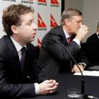 Alan Joyce, chief executive designate of Qantas, left, comments as CEO Geoff Dixon, right, and...