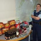 Alcohol harm reduction officer Tom Taylor, of Balclutha, stands next to alcohol confiscated by...