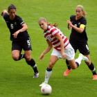 Alex Morgan (C), of the US, is chased by New Zealand's Abby Erceg (L) and Rebecca Smith during...