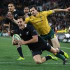 All Black fullback Israel Dagg crosses for a try despite the attentions of Wallabies winger Adam...