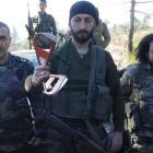 Alpaslan Celik (centre), a deputy commander in a Syrian Turkmen brigade, holds handles believed...