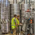 Alun Kilby (left) and winemaker Dave Sutton  at work in the Vinpro winery in Cromwell. Photo...