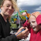 Amberrose Nicol (8), of Millers Flat, gets her face painted by Breana Horrell (14), of Te Anau,...
