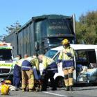 Ambulance, police and fire staff tend to the occupant of a vehicle involved in a collision on...
