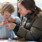 Amy Thorburn helps daughter Audrey (2) make a miniature steamship at the Swashbuckling Steamships...