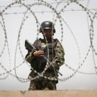 An Afghan soldier stands guard on a roof of one of the gates to Kabul's airport following a...