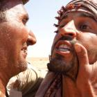An anti-Gaddafi fighter congratules another fighter after he captured a sniper at the Bani Walid...