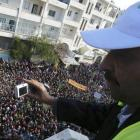 An Arab League observer takes photos of anti-government protesters on the streets in Adlb, Syria....