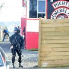 An Armed Offenders Squad member stands guard outside a Middleton Rd, Corstorphine, property which...