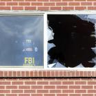 An FBI agent takes photographs inside the apartment of James Holmes, the suspect who opened fire...