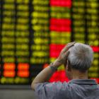 An investor looks at an electronic board showing stock information at a brokerage house in...