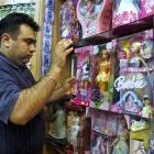 An Iranian shopkeeper displays dolls at his toy shop in Teheran. Police have closed down dozens...