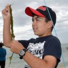 Anaru Jackson (11), of Christchurch, clears weed from his hook while fishing for trout at Taieri...