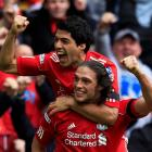 Andy Carroll (bottom) celebrates scoring for Liverpool against Everton with teammate Luis Suarez...
