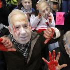 Anti-Israel demonstrators wear masks of Israeli Prime Benjamin Netanyahu as they sit at the...