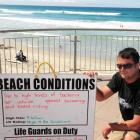 Antony Mason with the St Clair Surf Life Saving Club's sign warning against swimming at the beach...