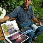 Photographer Barrie Wills looks through previous collections of his work. Photo by Rosie Manins.