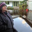 Aramoana League member Vicki Wilson stands next to one of about a dozen Aramoana properties which...