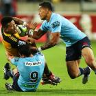 Ardie Savea of the Hurricanes is tackled by Nick Phipps and Israel Folau of the Waratahs during...