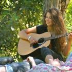 Aria Nader-Turner (16) plays the guitar while enjoying a spot out of the sun at the Whare Flat...