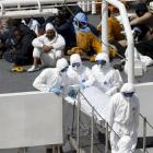 Armed Forces of Malta personnel  carry the body of a dead immigrant off Italian coastguard ship...
