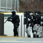 Armed offender squad members prepare to enter a Cromwell house suspected of being a...
