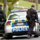 Armed offenders squad members leave a house in the Dunedin suburb of Wakari yesterday after an...