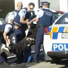 The youth is carried in handcuffs to a police car by (from left) Constable Louise Pearce,...