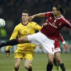 Arsenal's Laurent Koscielny (L) and AC Milan's Zlatan Ibrahimovic fight for the ball during their...