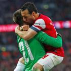 Arsenal's Santi Cazorla (R) celebrates with goalkeeper Lukasz Fabianski after scoring the winning...