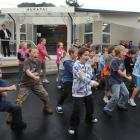 As rain begins to fall, Tainui School pupils perform a haka at the opening of the Hukatai, the...