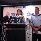 Australian Federal Police Deputy Commissioner Michael Phelan (R) listens as New South Wales...