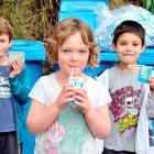 Babet Doherty (6) (centre) drinks milk at George Street Normal School yesterday while fellow...