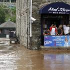 Bar patrons watch as the flooded Schuylkill River covers Main Street, in Manayunk, a suburb of...