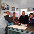 Barnes Oysters manager Graeme Wright serves Joan Black (left), who drove from Gore for her first...