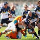 Ben Alexander of the Brumbies is chopped down by the Cheetahs' defence.  (Photo by Cameron...