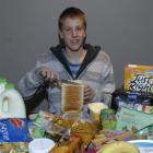 Ben Wardhaugh (14) with some of the food he and his three brothers consume in a week, in his...