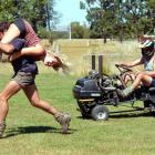 Bevan Wilson carries Hanna-Kaisa Ilhalainey and Kent Tisdall races a modified lawnmower in...