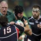 Blaine Scully of the US tackles Ireland's Stephen Ferris. REUTERS/Bogdan Cristel