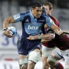 Blues Jerome Kaino looks to slip the tackle of Highlanders Jared Hoeata in a Super Rugby match at...