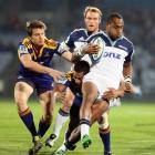 Blues player Joe Rokocoko in the tackle of Highlanders Ben Smith, left, and Alando Soakai. Credit...