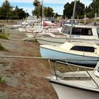 Boats at the Te Anau marina nosed up on dry land yesterday.  The level of Lake Te Anau has fallen...