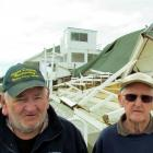 Bob Goodeve (left) and Dick Langford  in front of the wrecked  public stand last month. Photo by...
