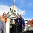 Bob White (left) and Martin Curtis prepare to reinstall the Cardrona School bell  in the restored...